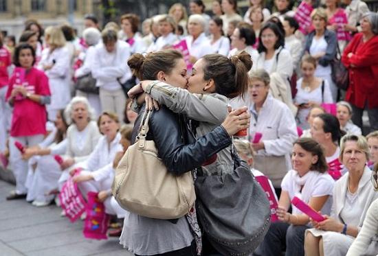 Casal de lésbicas se beija em frente a pessoas que participam de manifestação contra o casamento gay e adoções por casais do mesmo sexo, em Marselha, na França. O movimento Alliance VITA protestava contra a provável adoção de uma lei, a ser assinada no dia 31 de outubro, autorizando o casamento gay. Foto de Gérard Julien/AFP.