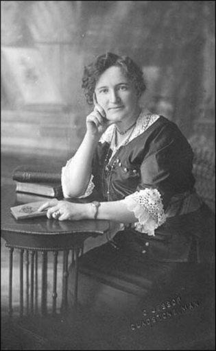 Nellie McClung, escritora em sua mesa de trabalho.  Foto de Cyril Jessop, copyright expirado. Disponível na Wikimedia Commons.