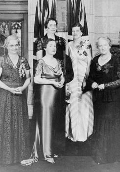 Foto da inauguração da placa comemorativa em homenagem as Cinco mulheres de Alberta, cuja luta garantiu às mulheres canadenses o direito de exercer cargos no Senado canadense. Nellie McClung na fila da frente à direita. Foto disponível na Wikimedia Commons em CC.