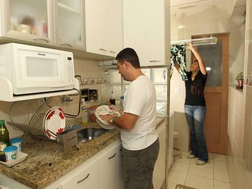 Lúcio Vieira, na cozinha, e Hosana Sauerbron, na área, nas tarefas domésticas. Foto: Carlos Ivan / Agência O Globo.