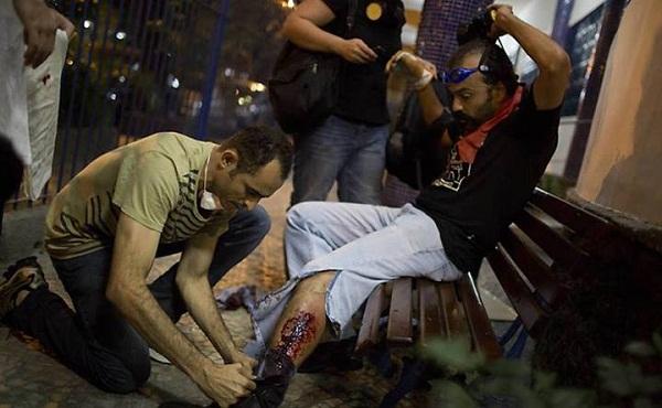 Manifestante baleado na perna recebe os primeiros socorros. Foto de Felipe Dana/Associated Press.