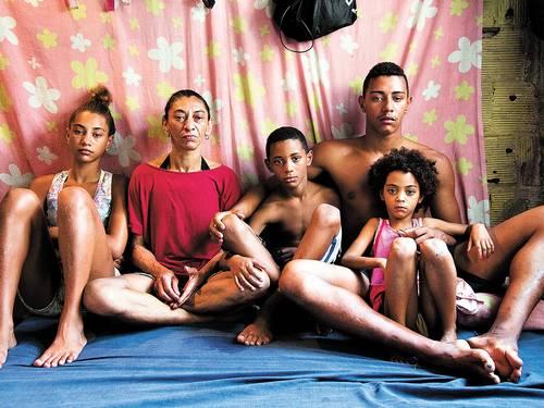 """Elizabete, mulher de Amarildo, com quatro dos seus seis filhos no barraco de um só cômodo onde a família mora na Rocinha: """"Eles (policiais) acham que pobre também é burro"""". Foto de Mônica Imbuzeiro / Agência O Globo."""