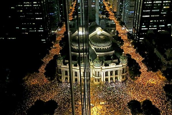 17 de junho - Reflexo em fachada de prédio mostra o protesto contra o aumento da passagem de ônibus no Rio de Janeiro, pela Avenida Rio Branco, chegando ao Teatro Municipal, no centro da cidade. Foto de Fabio Motta/ Estadão.