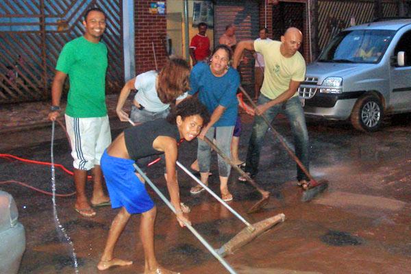 Moradores de via que margeia o Ribeirão Vermelho, na divisa de São Paulo com Osasco, se unem para a limpeza depois de mais uma enchente nesta terça-feira (Foto: Marcelo Mora/G1)