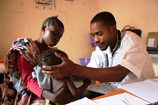 Profissional do grupo Médicos Sem Fronteiras examina jovem paciente no Congo. Foto de Emily Lynch/MSF.