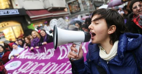 Mulher fala em megafone durante protesto em Istambul, na Turquia. A manifestação ocorre em virtude do Dia Internacional da Mulher. Foto de Ozan Kose/AFP.