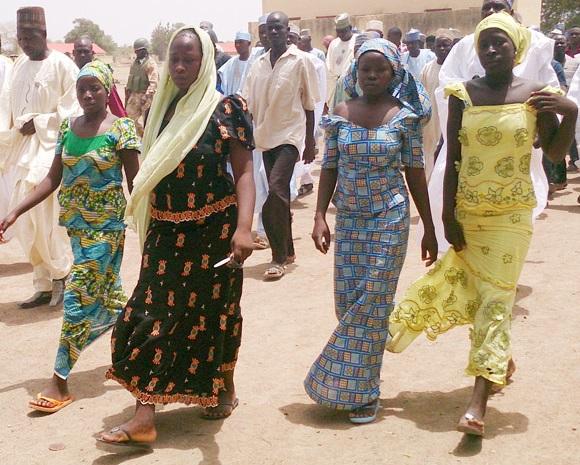Quatro estudantes caminham em Chibok, após fugirem do grupo Boko Haram. Foto de Haruna Umar/AP.
