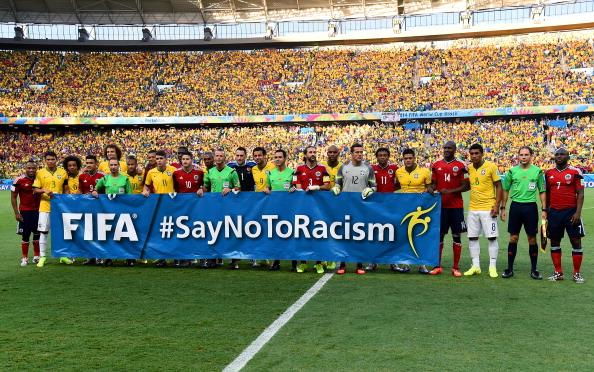 """Jogadores de Brasil e Colômbia seguram o banner da campanha """"Say no to Racism"""" da FIFA, antes do jogo. Foto de Lars Baron/ Getty Images."""