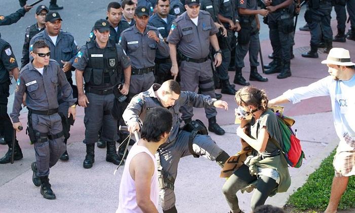 Policial chuta manifestante durante protesto na Saens Peña (RJ). Foto de Marcelo Piu / Agência O Globo.