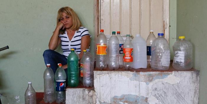 A auxiliar de servicos Eliziete Feitosa Sampaio, 47, mostra as garrafas que junta para ir até a bica buscar água na cidade de Itu (a 101 km de São Paulo). Foto de Moacyr Lopes Junior/Folhapress.