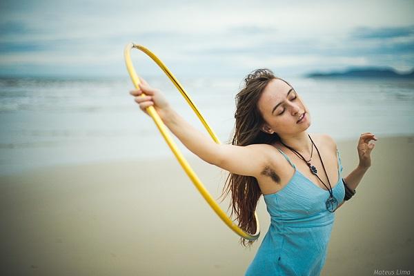Julia Guadagnucci com um bambolê na praia. Foto de Mateus Lima.