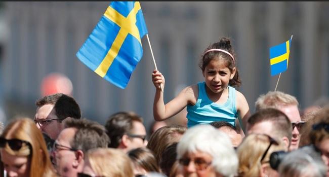 Menina segura bandeira da Suécia em Estocolmo. Foto de Jonathan Nackstrand/AFP.