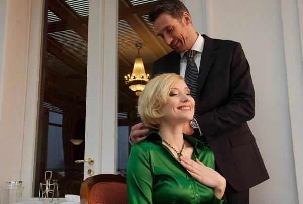 Homem coloca um colar no pescoço de uma mulher. Imagem de Stock4B/Corbis.
