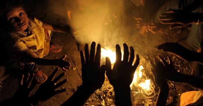 Moradores de rua se aquecerem em volta de fogueira em Calcutá, Índia. Foto de Deshakalyan Chowdhur/AFP.