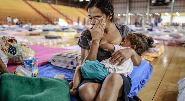 Mulher e criança, desabrigadas após o rompimento da barragem de rejeitos da mineradora Samarco, em um abrigo em Mariana, interior de Minas Gerais. Foto de Cristiane Mattos/Futura Press/Estadão.